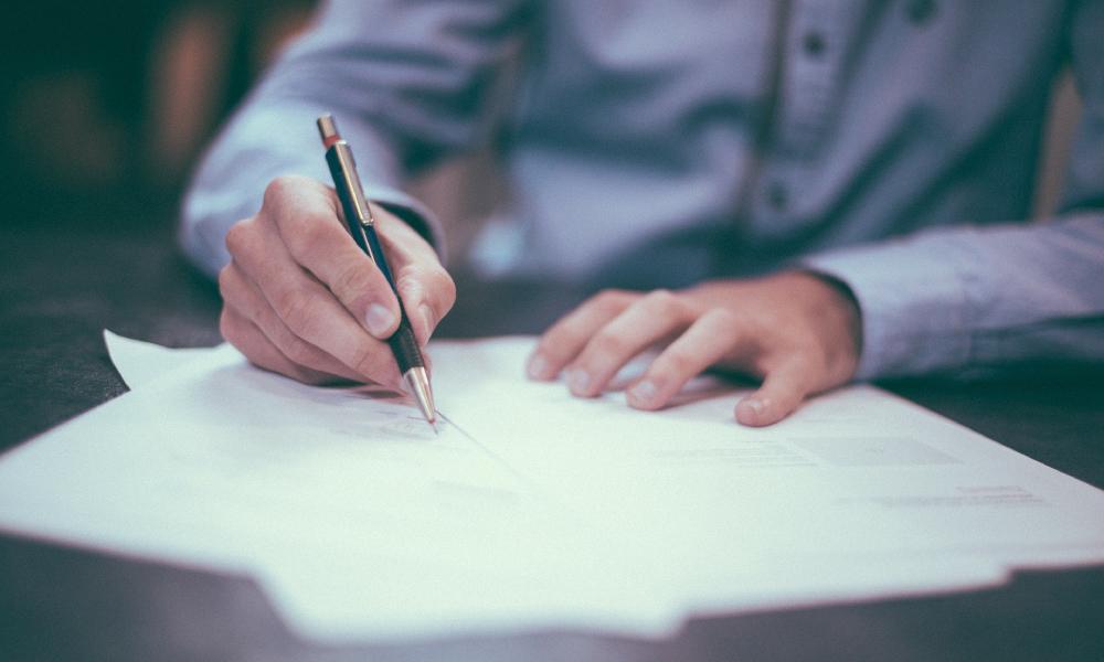 homem assinando um documento
